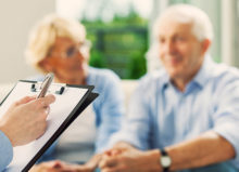 Senior couple having meeting with financial advisor or insurance agent. Close up of female hand holding pen and clipboard.